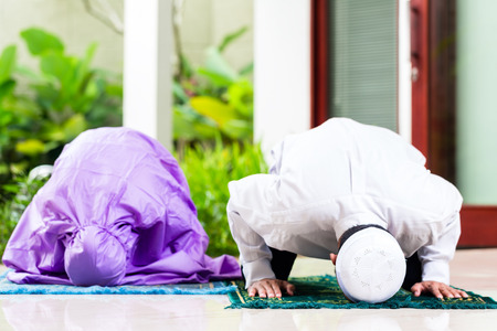 Asian Muslim couple, man and woman, praying at home sitting on prayer carpet in their house in front of the tropical garden