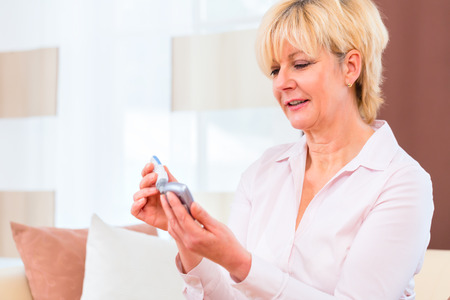 Woman with adult onset diabetes measuring blood sugar with indicator