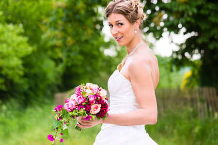 Bride in dress with bridal bouquet in garden waiting for wedding