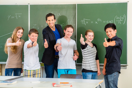 Photo pour School and education - Teacher and students stand in front of a blackboard with math work in a classroom or class - image libre de droit
