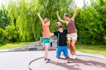 Family playing miniature golf outdoors