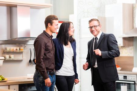 Photo pour Man and woman consult salesman for domestic kitchen in studio or furniture store - image libre de droit
