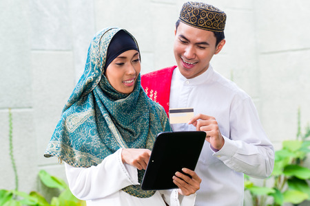 Asian Muslim man and woman shopping online paying with credit card on tablet PC