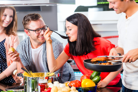 Friends cooking spaghetti and meat in domestic kitchen