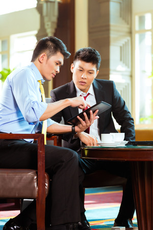 Two Asian Chinese businessman or office people having a business meeting in a hotel lobby discussing documents on a tablet computer while drinking coffeeの写真素材