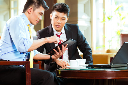 Two Asian Chinese businessman or office people having a business meeting in a hotel lobby discussing documents on a tablet computer while drinking coffee