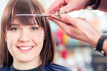 Hairdresser cutting woman bangs hair in shop