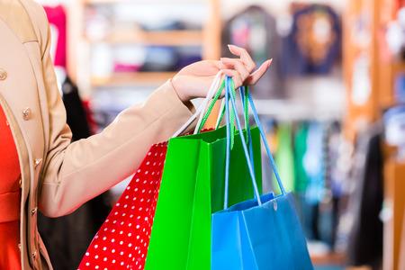 Photo pour Woman with shopping bags in shop - image libre de droit