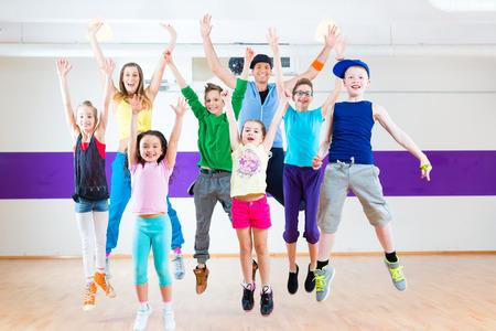 Dance teacher giving children fitness class in gym