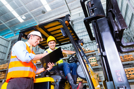 Photo for Asian fork lift truck driver discussing checklist with foreman in warehouse - Royalty Free Image