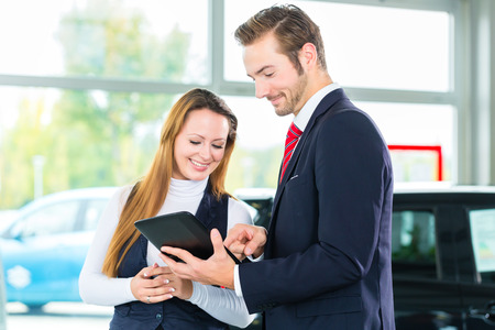 Seller or car salesman and female client or customer in car dealership presenting the interior decoration of new and used cars in the showroom on tablet computer