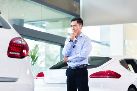 Asian man buying luxury car in dealership