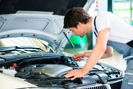 Auto mechanic working in car service workshop