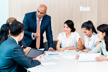 Photo for Diversity team in business development meeting with charts, Indian CEO and Caucasian executive crunching numbers, charts and figures on the desk - Royalty Free Image