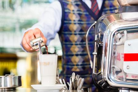 Barista in cafe or coffee bar preparing pouring espresso shot in glass of latte macchiato