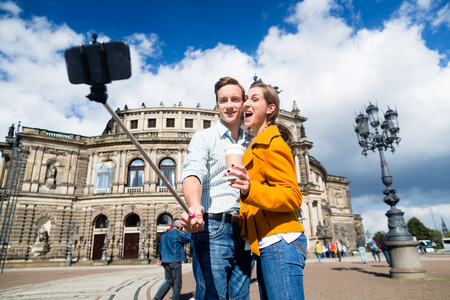 Tourist couple at Semperoper in Dresden taking selfie with phone on stick