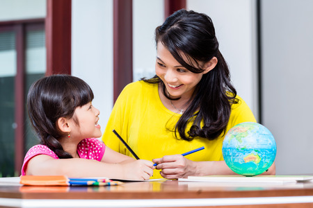 Chinese mother doing school homework with child or homeschooling daughter