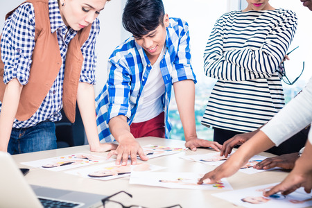 Advertising agency team choosing model for campaign among pictures spread out on table