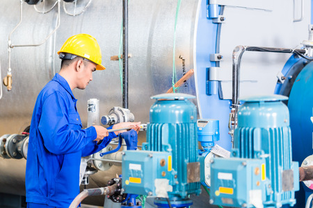 Technician in Asian factory at machine maintenance working with wrench