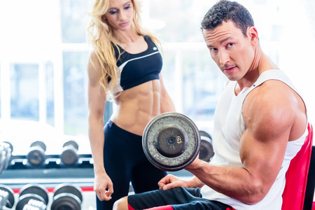 Foto de Couple in fitness gym with dumbbells lifting weight as sport, man and woman training together - Imagen libre de derechos