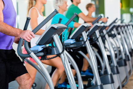 Foto de Group with senior and young men and women on elliptical treadmill trainer in fitness gym exercising - Imagen libre de derechos