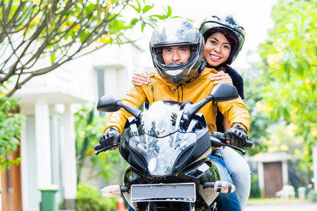 Photo for Couple with helmets riding motorcycle, wife is sitting behind her husband - Royalty Free Image