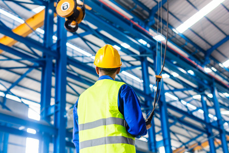 Worker in factory controlling crane with remote