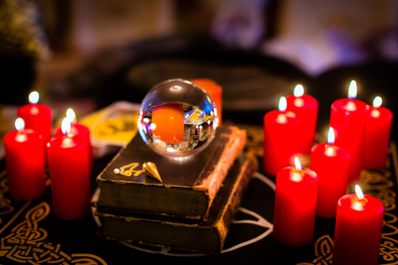 Crystal ball to prophesy or esoteric clairvoyance during a Seance in the candle light