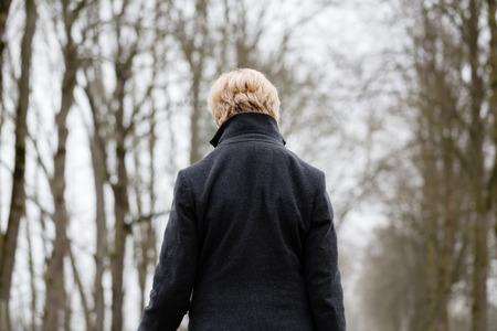 Depressed or sad woman walking down a barren path in winter
