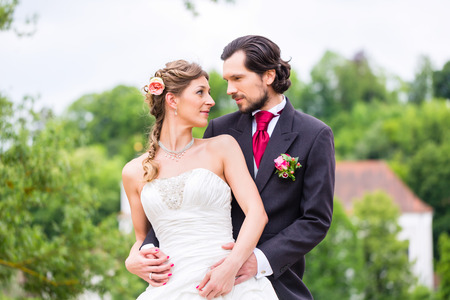 Wedding bride and groom outside in the garden, groom embracing bride