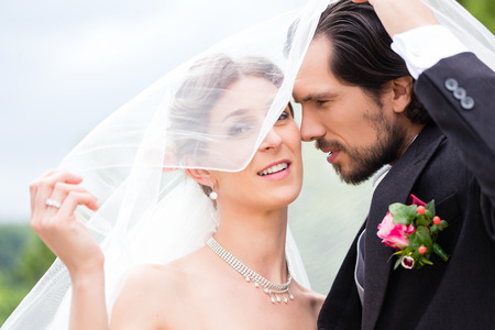 Wedding couple bride and groom hiding under veil