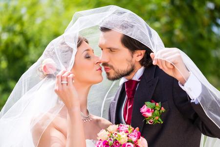 Bridal pair kissing under veil at wedding