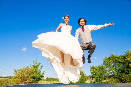 Wedding bride and groom jumping on trampoline having fun
