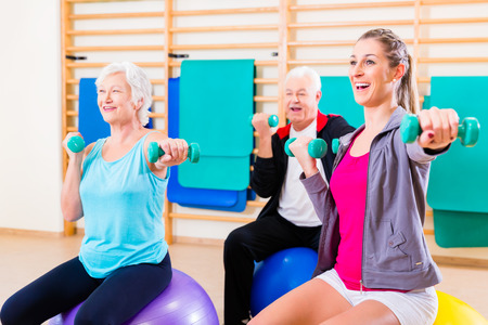 Group of senior and young people at physiotherapy doing exercises