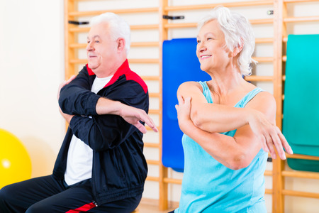 Senior people in fitness exercise doing gymnastic stretching