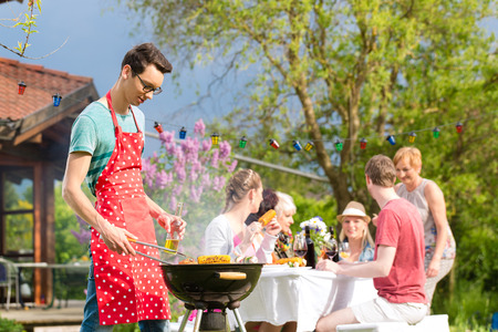 Photo for Family and friends having bbq at garden party, man in the foreground on grill, in background people drinking and eating - Royalty Free Image