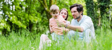 Foto de Family with son on meadow blowing dandelion seed - Imagen libre de derechos
