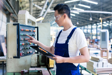Photo for Worker pressing buttons on CNC machine control board in Asian factory - Royalty Free Image
