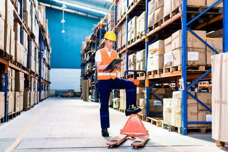 Asian man in industrial warehouse checking list