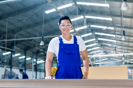 Photo for Asian carpenter standing in workshop with wood boards looking at the camera - Royalty Free Image