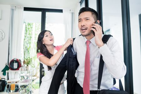 Wife helping man being late for work in jacket, the couple is in a hurry