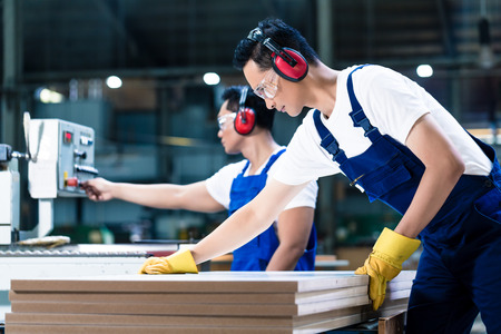 Photo for Two wood workers in carpentry cutting boards putting them in saw - Royalty Free Image