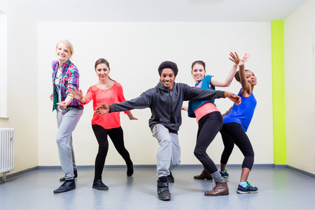 Group of young people having dance class in gym