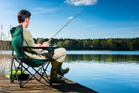 Photo pour Man fishing at lake sitting on jetty close to the water - image libre de droit