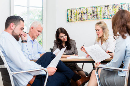 Lawyers having team meeting in law firm reading documents