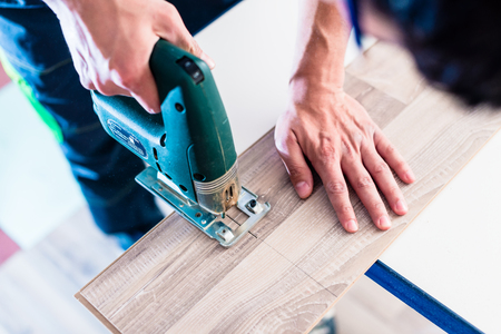 DIY worker cutting wooden panel with jig saw