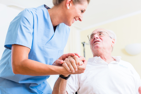 Nurse holding hand of senior man in rest home