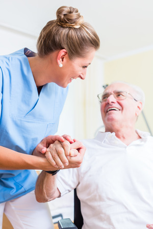 Photo pour Nurse holding hand of senior man in rest home - image libre de droit