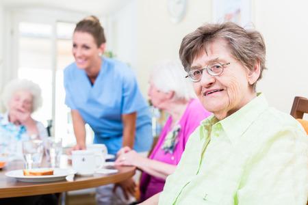 Photo pour Group of seniors having food in nursing home, a nurse is serving - image libre de droit