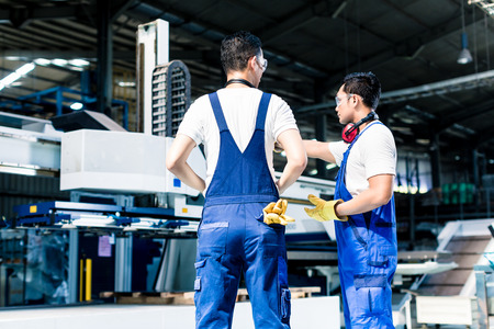 Photo for Worker team in factory discussing in front of machine - Royalty Free Image